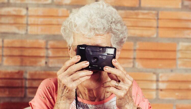 Une dame âgée tenant un appareil photo
