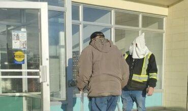 Un homme portant une capuche à la KKK devant un bureau de poste