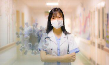 Femme docteure dans un corridor d'hôpital, portant un masque avec le signe du virus de la COVID-19,