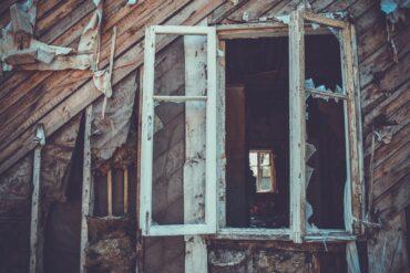 Une maison en bois avec une fenêtre calcinée.