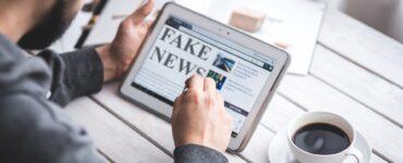Un homme sur une tablette lit de l'information. Le contenu de l'écran indique fake news. Une tasse de café est posée à côté.